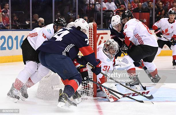 J Oshie of Team USA wraps the puck around the net on Carey Price with Jay Bouwmeester of Team Canada chasing during the World Cup of Hockey 2016 at...