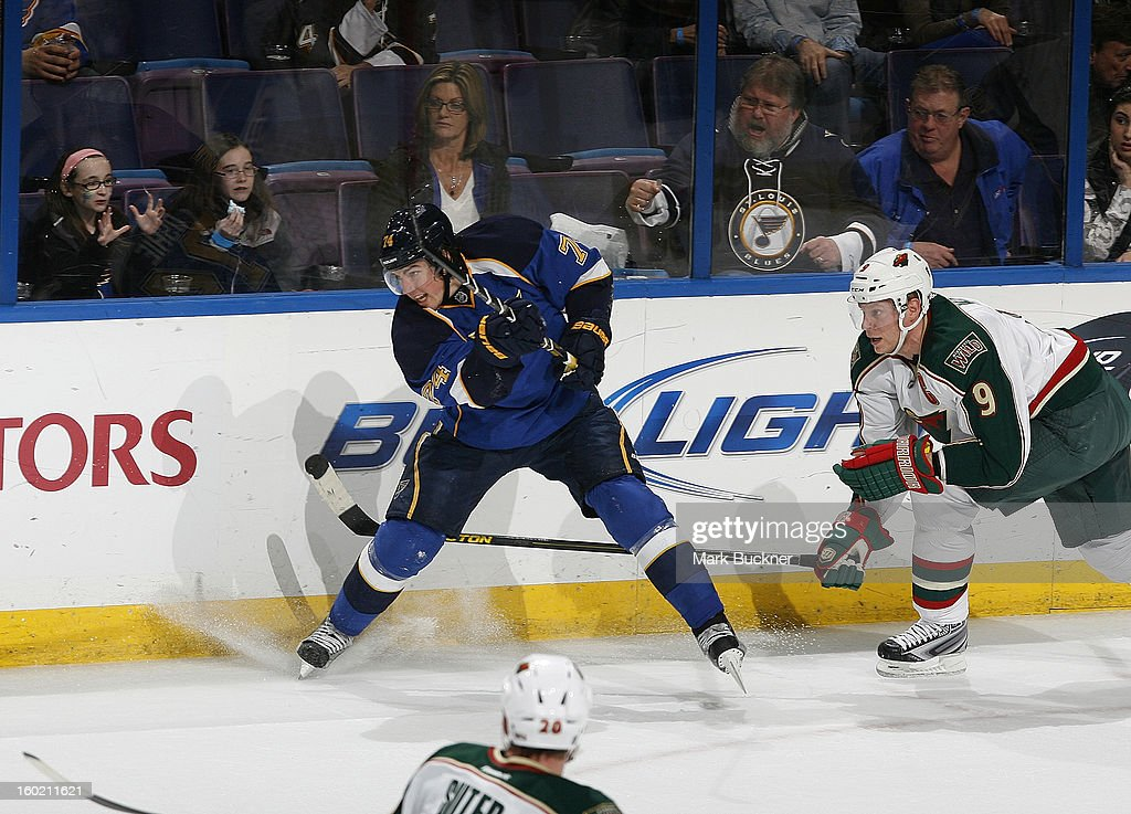 T.J. Oshie #74 of the St. Louis Blues clears the puck away from Mikko Koivu #9 of the Minnesota Wild in an NHL game on January 27, 2013 at Scottrade Center in St. Louis, Missouri.