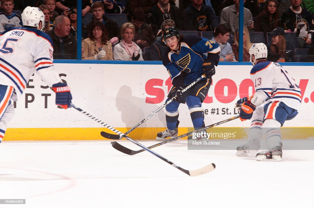 T.J. Oshie #74 of the St. Louis Blues handles the puck as Mike Brown #13 of the Edmonton Oilers defends in an NHL game on March 26, 2013 at Scottrade Center in St. Louis, Missouri.