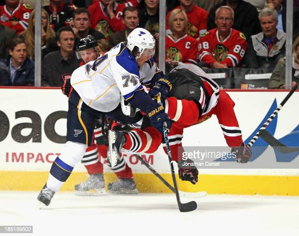 J Oshie of the St Louis Blues hits Marian Hossa of the Chicago Blackhawks at the United Center on October 17 2013 in Chicago Illinois The Blues...