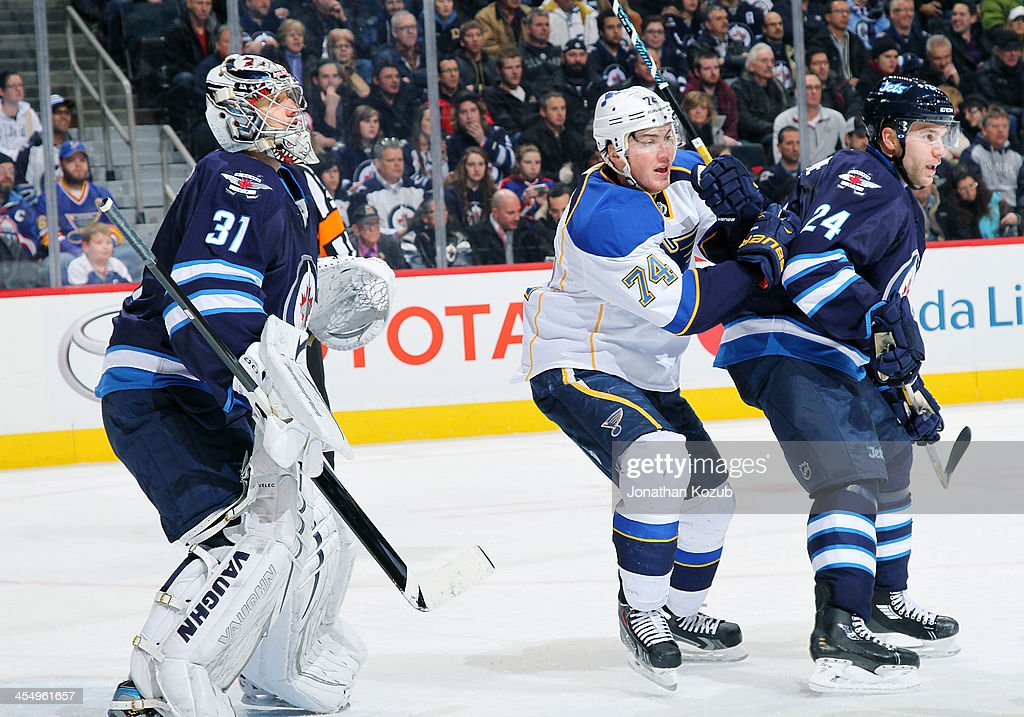 J Oshie of the St Louis Blues positions himself between goaltender Ondrej Pavelec and Grant Clitsome of the Winnipeg Jets as they keep an eye on the...