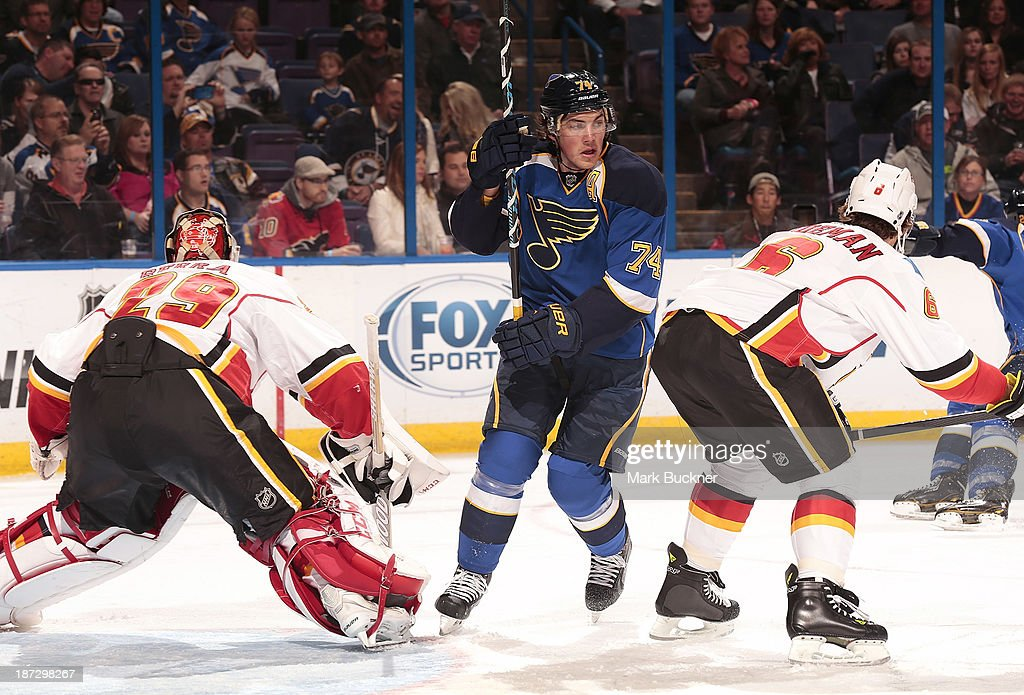 T.J. Oshie #74 of the St. Louis Blues skates between goalie Reto Berra #29 and Dennis Wideman #6 of the Calgary Flames on November 7, 2013 at Scottrade Center in St. Louis, Missouri.