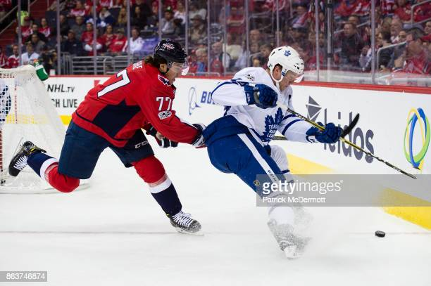J Oshie of the Washington Capitals and Morgan Rielly of the Toronto Maple Leafs battle for the puck in the first period at Capital One Arena on...