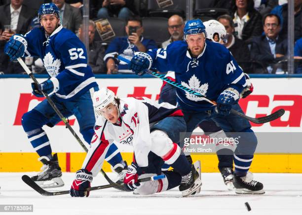 J Oshie of the Washington Capitals battles for the puck with Martin Marincin and Leo Komarov of the Toronto Maple Leafs during the first period in...
