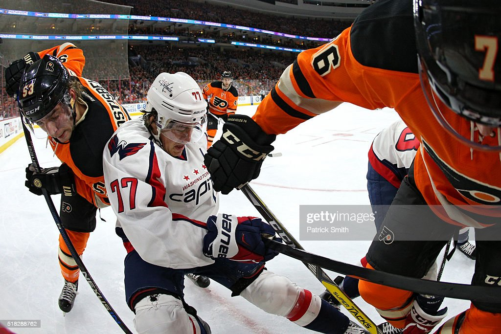 T.J. Oshie #77 of the Washington Capitals is checked by Chris VandeVelde #76 and Shayne Gostisbehere #53 of the Philadelphia Flyers during the first period at Wells Fargo Center on March 30, 2016 in Philadelphia, Pennsylvania.