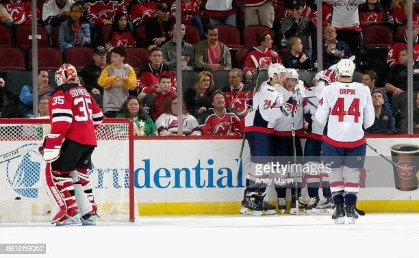 J Oshie of the Washington Capitals is congratulated by his teammates after scoring a firstperiod goal as Cory Schneider of the New Jersey Devils...