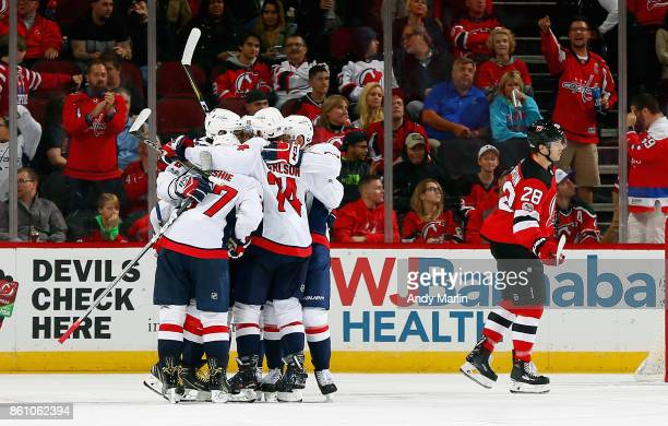 J Oshie of the Washington Capitals is congratulated by his teammates after scoring a goal against the New Jersey Devils during the game at Prudential...