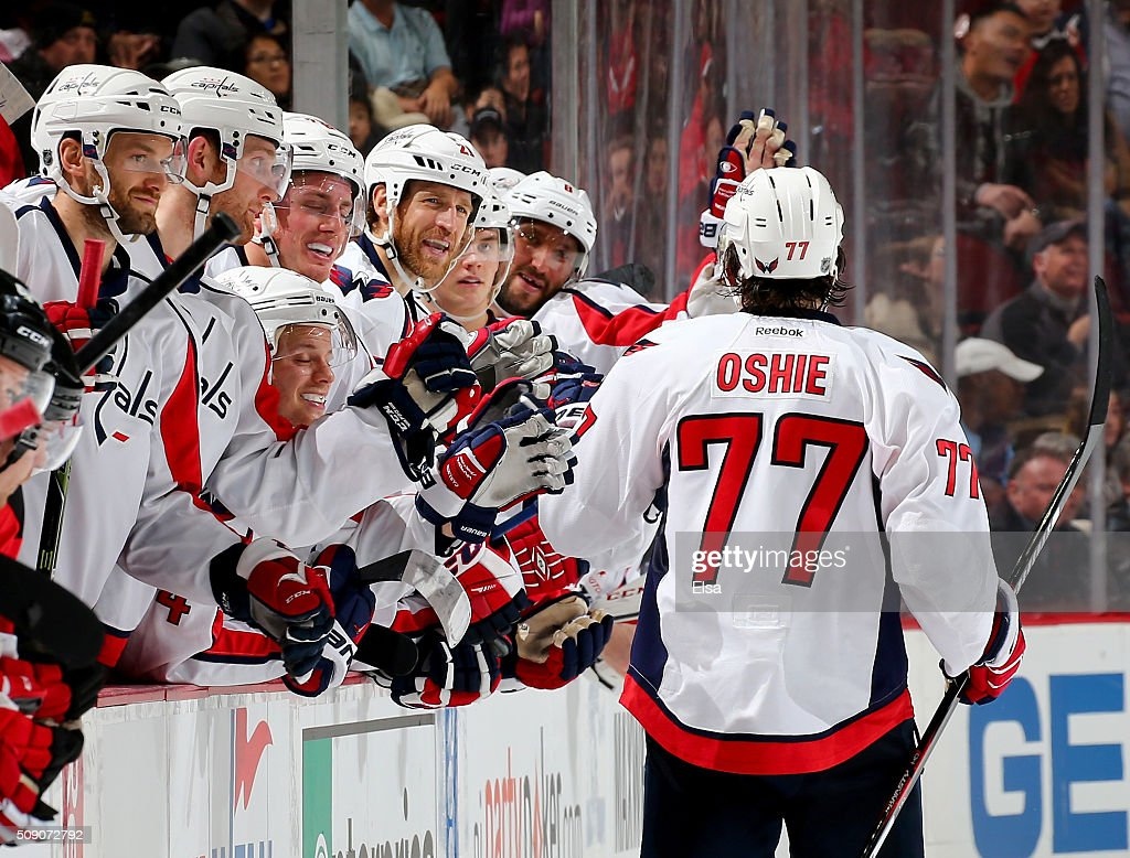 T.J. Oshie #77 of the Washington Capitals is congratulated by teammates on the bench after he scored a goal in the overtime shootout against the New Jersey Devils on February 6, 2016 at Prudential Center in Newark, New Jersey.The Washington Capitals defeated the New Jersey Devils 3-2 in an overtime shootout.
