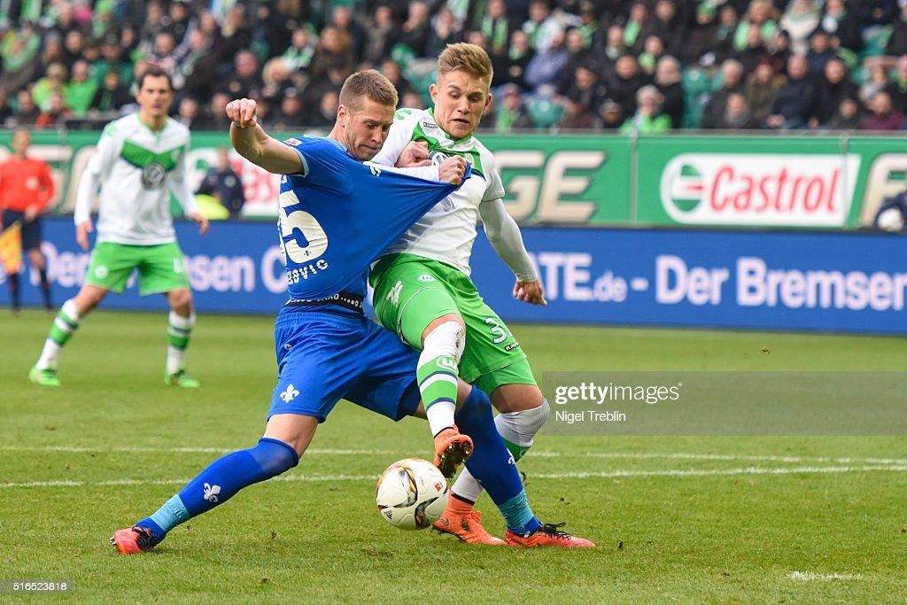 Oskar Zawanda of Wolfsburg is challenged by Slobodan Rajkovic of Darmstadt during the Bundesliga match between VfL Wolfsburg and Hertha BSC Berlin at Volkswagen Arena on March 19, 2016 in Wolfsburg, Germany.