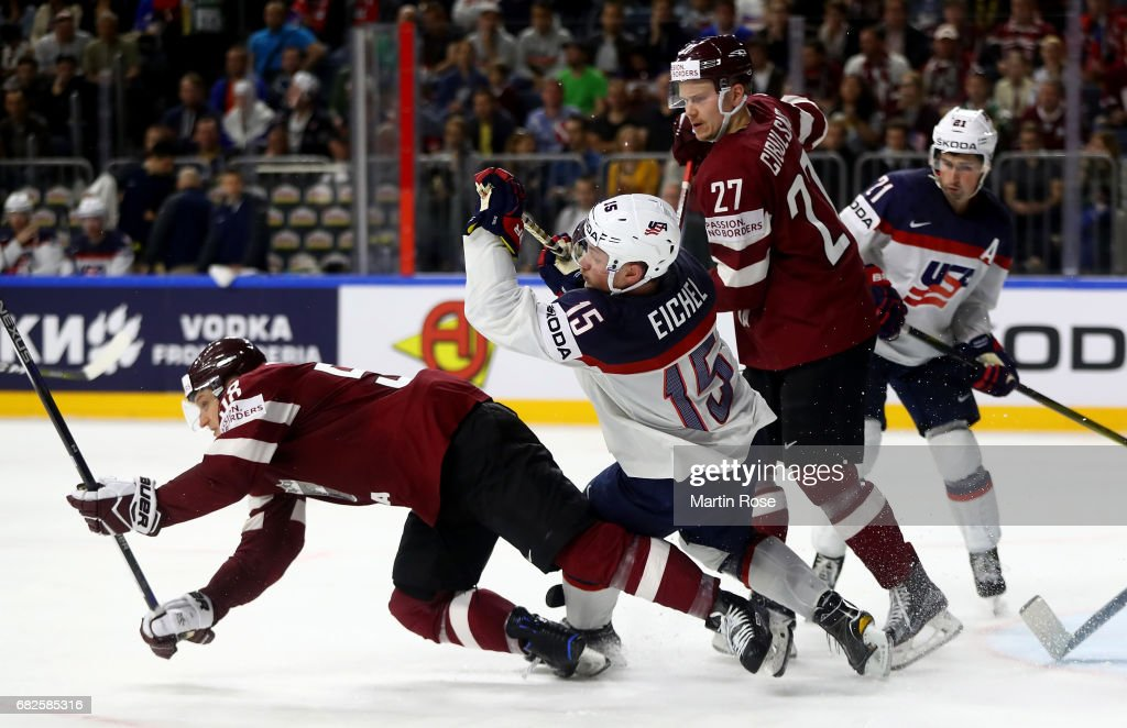 Oskars Cibulskis #27 of Latvia challenges Jack Eichel of the United States for the puck during the 2017 IIHF Ice Hockey World Championship game between Latvia and the United States at Lanxess Arena on May 13, 2017 in Cologne, Germany.