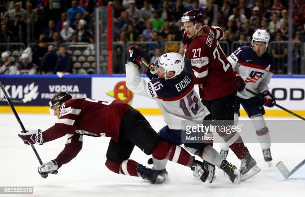 Oskars Cibulskis of Latvia challenges Jack Eichel of the United States for the puck during the 2017 IIHF Ice Hockey World Championship game between...
