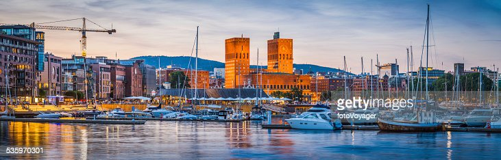 Oslo harbour Aker Brygge City Hall illuminated at dusk Norway : Stock Photo