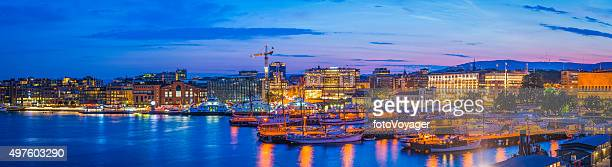 Oslo harbour sunset illuminated landmarks Aker Brygge waterfront panorama Norway