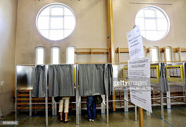Women stand in booths before casting their votes in Norway's general election at a school in Oslo 12 September 2005 Norwegians are deciding who will...