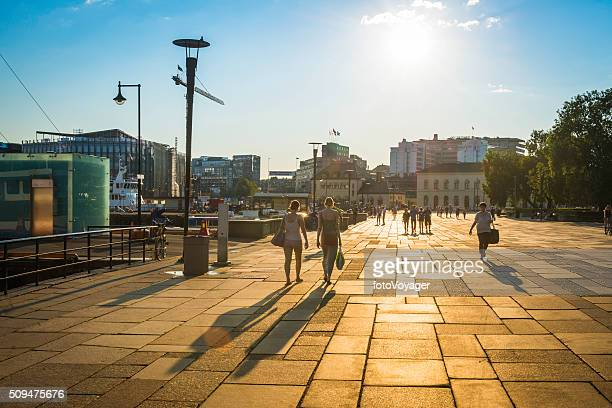 Oslo summer sunlight and shadows people strolling harbour waterfront Norway