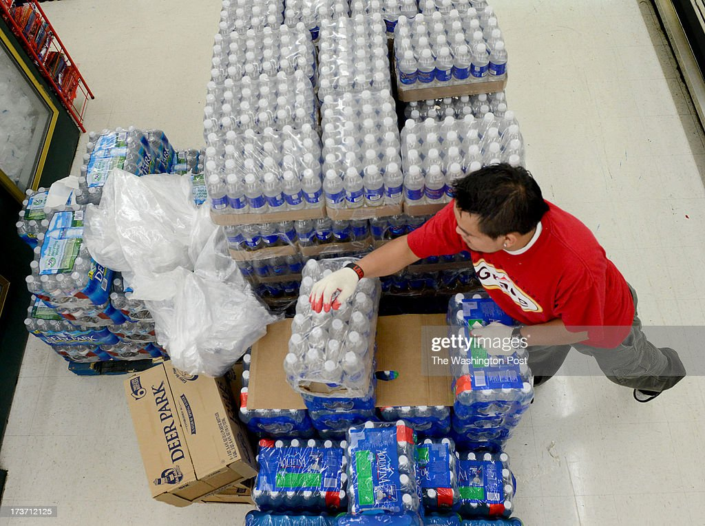Osman Raul restocks drinking water at Jumbo Foods International Supermarket in Temple Hills, MD on July 16, 2013. The supermarket is well stocked for water because the manager had warehoused water, along with other emergency supplies, in preparation for the summer storm season. Later today the Washington Suburban Sanitary Commission will shut down a water main that will cut water to thousands of residents and businesses in southern Prince George's County. The shutoff is necessary to make much-need repairs. WSSC officials say the outage will run 2-4 days WSSC officials say. They're advising residents to stock up on water, fill bathtubs to use for flushing, and ration water as much as necessary.