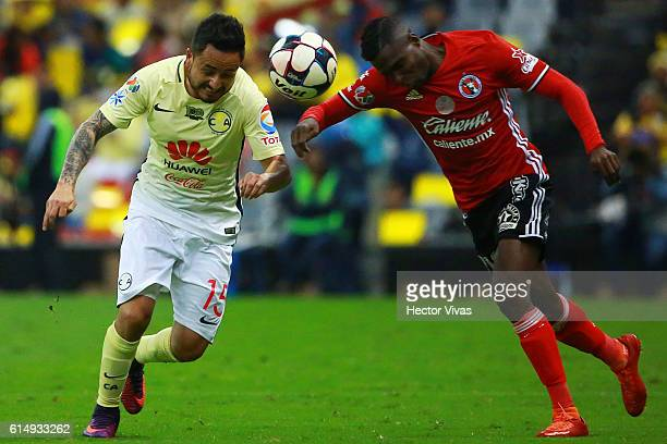Osmar Mares of America struggles for the ball with Aviles Hurtado of Tijuana during the 13th round match between America and Tijuana as part of the...