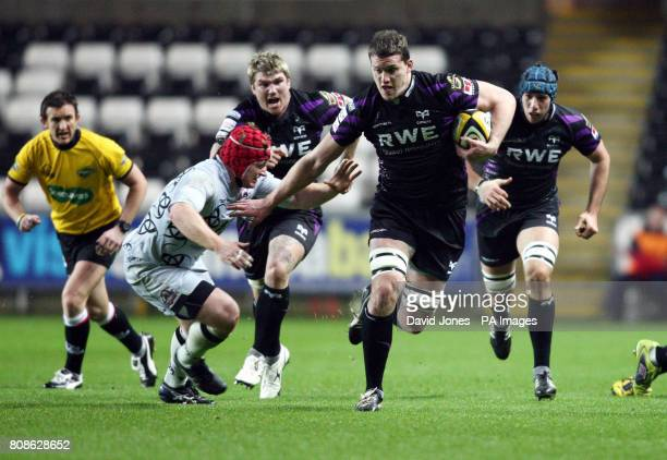 Ospreys' Ian Evans hands off Edinburgh's Kyle Traynor during the Magners League match at the Liberty Stadium Cardiff
