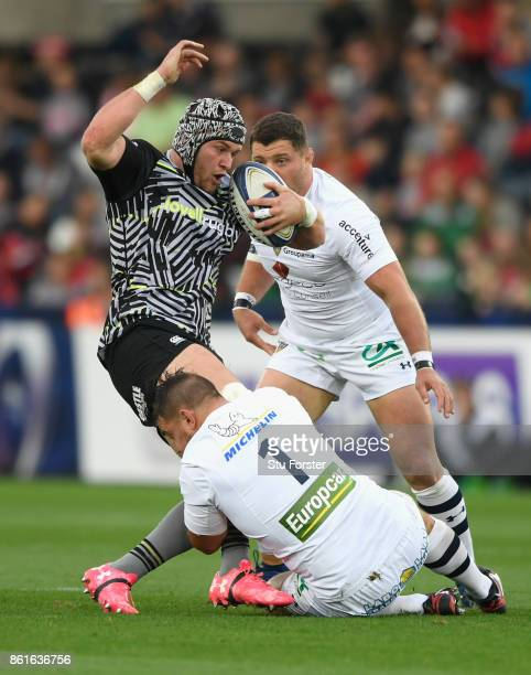 Ospreys player Dan Lydiate is tackled by Raphael Chaume during the European Rugby Champions Cup match between Ospreys and ASM Clermont Auvergne at...