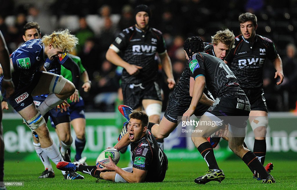 Ospreys scrum half Rhys Webb (c) gets the ball away despite the attentions of <a gi-track='captionPersonalityLinkClicked' href=/galleries/search?phrase=Richie+Gray+-+Rugby+Player&family=editorial&specificpeople=5907993 ng-click='$event.stopPropagation()'>Richie Gray</a> (l) during the Heineken Cup pool 1 round 4 match between Ospreys and Castres Olympique at Liberty Stadium on December 13, 2013 in Swansea, Wales.