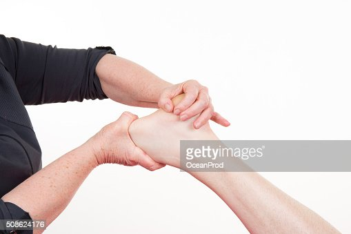 Osteopath doing reflexology massage on male foot against colorful background. : Stock Photo