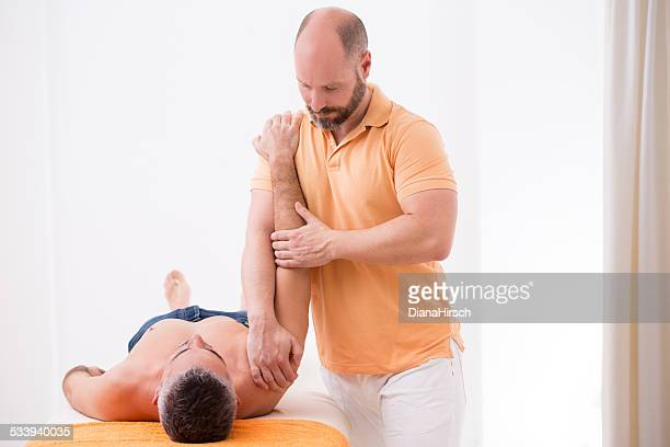 osteopath practising  physical therapy with patient