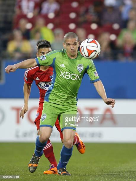 Osvaldo Alonso of Seattle Sounders FC pushes the ball up the field as Mauro Diaz of FC Dallas follows behind at Toyota Stadium on April 12 2014 in...