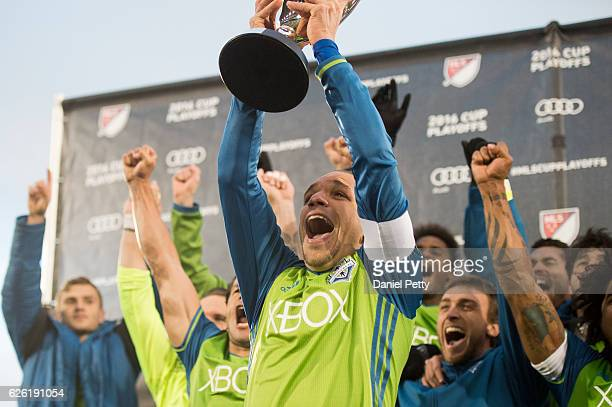 Osvaldo Alonso of Seattle Sounders hoists the Western Conference trophy after the team defeated the Colorado Rapids during the second leg of the...