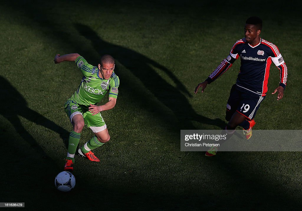 Osvaldo Alonso #6 of the Seattle Sounders controls the ball past Clyde Simms #19 of the New England Revolution during the the first half of the FC Tucson Desert Diamond Cup at Kino Sports Complex on February 13, 2013 in Tucson, Arizona. The Sounders defeated the Revolution 2-0.
