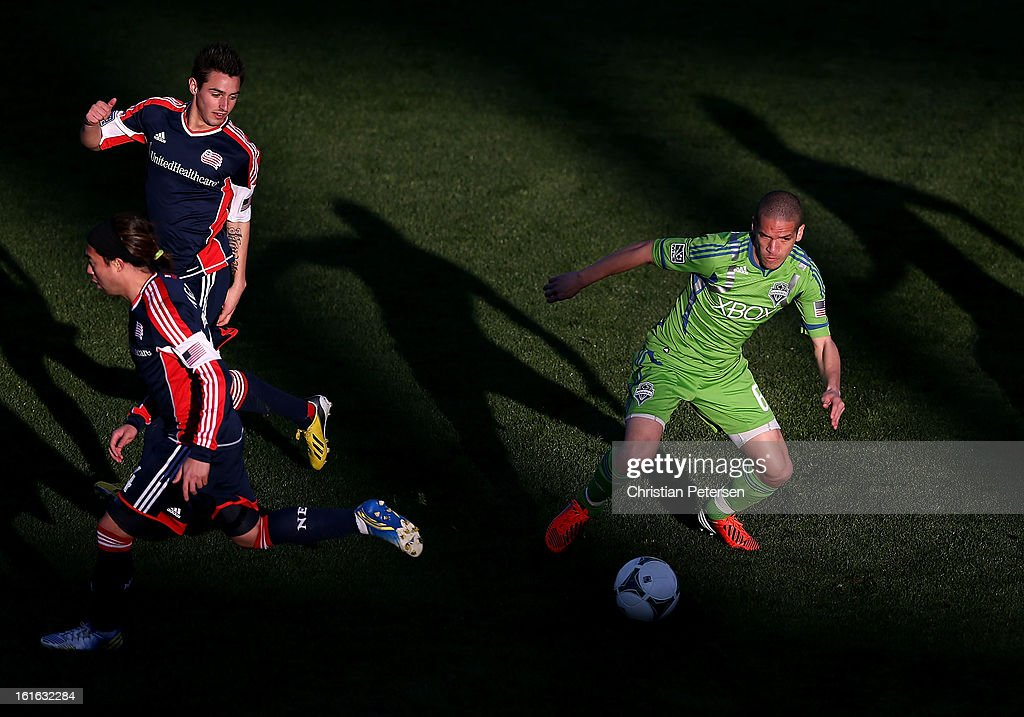 Osvaldo Alonso #6 of the Seattle Sounders controls the ball past Diego Fagundez #14 and Lee Nguyen #24 of the New England Revolution during the the first half of the FC Tucson Desert Diamond Cup at Kino Sports Complex on February 13, 2013 in Tucson, Arizona.