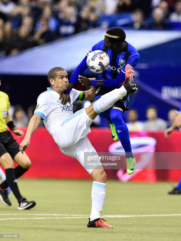 Osvaldo Alonso #6 of the Seattle Sounders kicks the ball as Ambroise Oyongo #2 of the Montreal Impact jumps in the air for a block during the MLS game at Olympic Stadium on March 11, 2017 in Montreal, Quebec, Canada. The Seattle Sounders FC and the Montreal Impact end up in a 2-2 draw.
