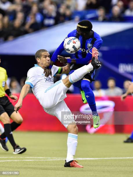 Osvaldo Alonso of the Seattle Sounders kicks the ball as Ambroise Oyongo of the Montreal Impact jumps in the air for a block during the MLS game at...