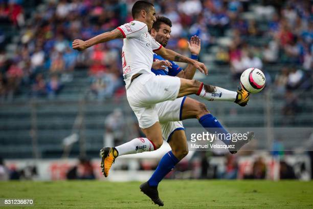 Osvaldo Gonzalez of Toluca struggles for the ball against Martin Cauteruccio of Cruz Azul during the 4th round match between Cruz Azul and Chivas as...