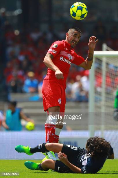 Osvaldo Gonzalez of Toluca struggles for the ball with Matias Britos of Pumas during the 13th round match between Pumas UNAM and Toluca as part of...