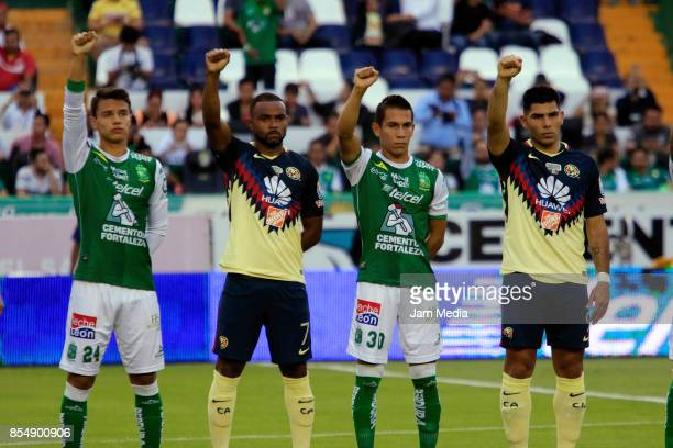 Osvaldo Rodriguez of Leon William of America and Jose Rodriguez of Leon and Silvio Romero of America raise their fists during a minute of silence for...