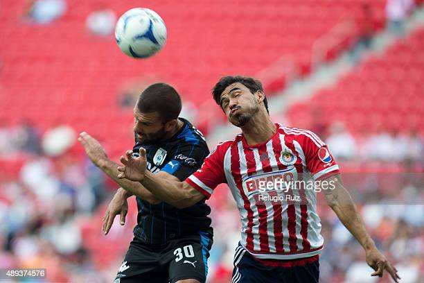 Oswaldo Alanis of Chivas jumps for the ball with Emanuel Villa of Queretaro during a 9th round match between Chivas and Queretaro as part of the...