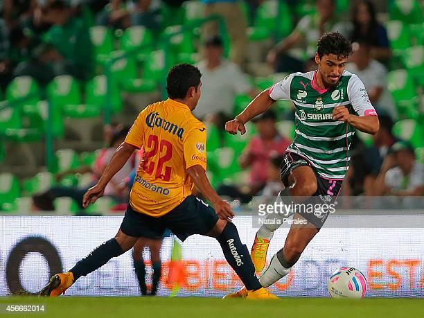 Oswaldo Alanis of Santos dribbles Armando Zamorano during a match between Santos Laguna and Morelia as part of 12th round Apertura 2014 Liga MX at...