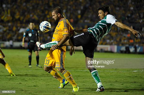 Oswaldo Alanis of Santos fights for the ball with Emanuel 'Tito' Villa of Tigres during a semifinal match between Tigres UANL and Santos Laguna as...