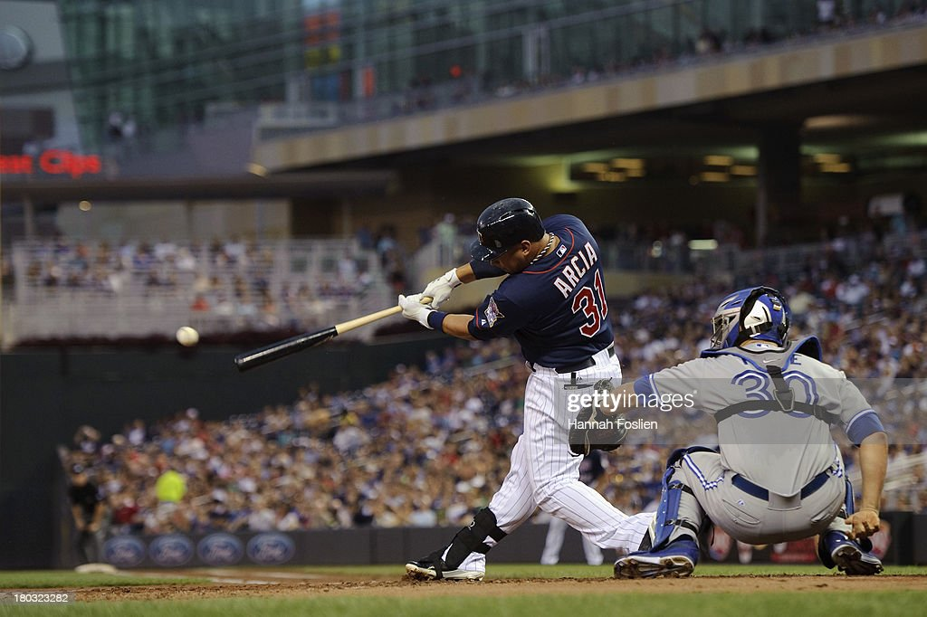 <a gi-track='captionPersonalityLinkClicked' href=/galleries/search?phrase=Oswaldo+Arcia&family=editorial&specificpeople=8948415 ng-click='$event.stopPropagation()'>Oswaldo Arcia</a> #31 of the Minnesota Twins bats as <a gi-track='captionPersonalityLinkClicked' href=/galleries/search?phrase=Josh+Thole&family=editorial&specificpeople=5741573 ng-click='$event.stopPropagation()'>Josh Thole</a> #30 of the Toronto Blue Jays catches during the game on September 6, 2013 at Target Field in Minneapolis, Minnesota.