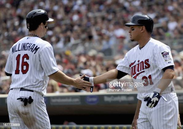 Oswaldo Arcia of the Minnesota Twins congratulates teammate Josh Willingham on a scoring a run against the Texas Rangers during the fourth inning of...