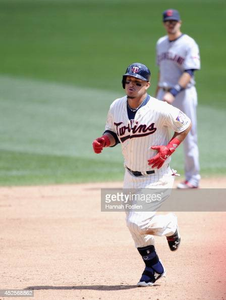 Oswaldo Arcia of the Minnesota Twins rounds the bases after hitting a solo home run as Lonnie Chisenhall of the Cleveland Indians looks on during the...