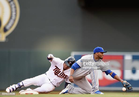 Oswaldo Arcia of the Minnesota Twins slides into second base safely to second base with a double as the throw passes Alcides Escobar of the Kansas...