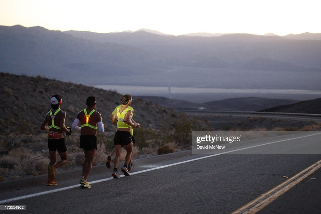 Oswaldo Lopez (C) of Madera, California and Carlos Alberto of Portugal (R) run wearing headlamp near Panamint Springs as night falls during the AdventurCORPS Badwater 135 ultra-marathon race on July 15, 2013 in Death Valley National Park, California. Billed as the toughest footrace in the world, the 36th annual Badwater 135 starts at Badwater Basin in Death Valley, 280 feet below sea level, where athletes begin a 135-mile non-stop run over three mountain ranges in extreme mid-summer desert heat to finish at 8,350-foot near Mount Whitney for a total cumulative vertical ascent of 13,000 feet. July 10 marked the 100-year anniversary of the all-time hottest world record temperature of 134 degrees, set in Death Valley where the average high in July is 116. A total of 96 competitors from 22 nations are attempting the run which equals about five back-to-back marathons.