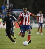 Oswaldo Minda of Chivas USA dribbles the ball up field chased by Marvin Chavez of the San Jose Earthquakes in the second half of an MLS soccer game...