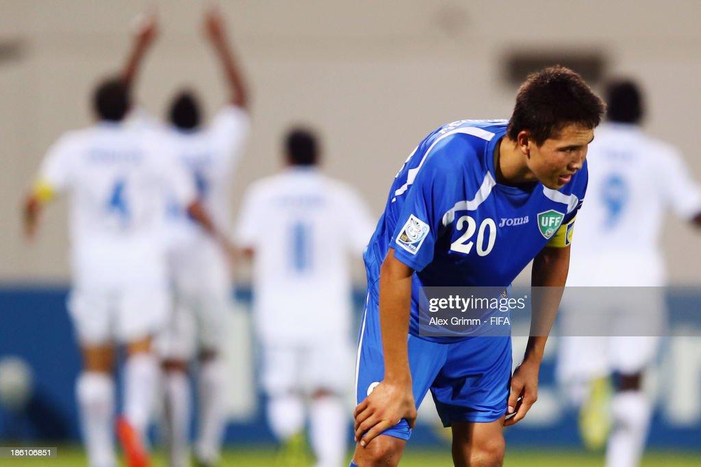 Otabek Shukurov of Uzbekistan reacts as Jorge Bodden of Honduras celebrates his team's first goal with team mates during the FIFA U-17 World Cup UAE 2013 Round of 16 match between Honduras and Uzbekistan at Sharjah Stadium on October 28, 2013 in Sharjah, United Arab Emirates.