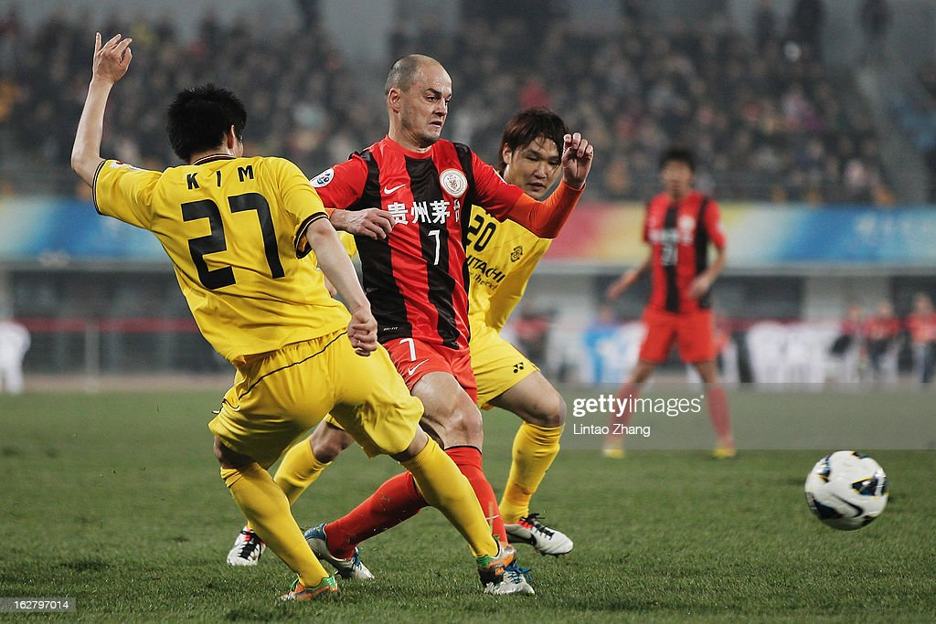 Otani (C) of Guizhou Renhe challenges Kim Chang Soo (L) and Akimi Barada of Kashiwa Reysol during the AFC Champions League match between Guizhou Renhe and Kashiwa Reysol at Olympic Sports Center on February 27, 2013 in Guiyang, China.