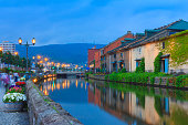 Otaru, Japan historic canal and warehouse in summer twilight time, people are walking alongside the canal, famous tourist attraction of Sapporo, Hokkaido.