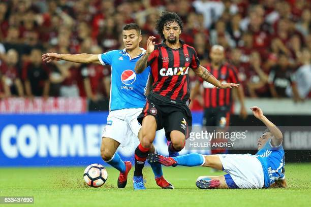 Otavio from Brazil's Atletico Paranaense struggles for the ball with Jhon Duque and Maxi Nunez from Colombia's Millonarios during their Libertadores...