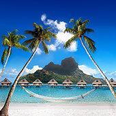 View of the Otemanu mountain through the palms with hammock and ocean. Bora-Bora. Polynesia