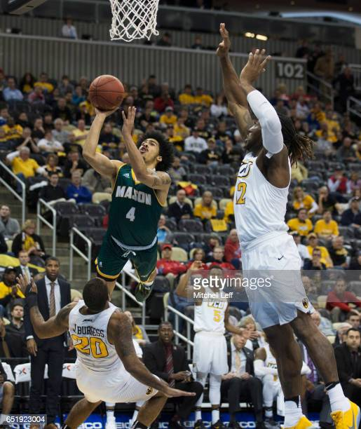Otis Livingston II of the George Mason Patriots shoots the ball against Jordan Burgess and Mo AlieCox of the Virginia Commonwealth Rams in the...